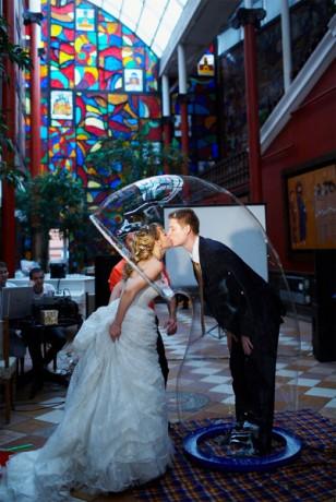 Жених и невеста в мыльном пузыре на свадьбе