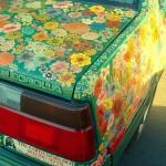 Зеленое авто, усыпанное полевыми цветами