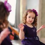 Девочка в фиолетовом платье с фиолетовым бантом
