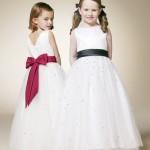 Девочки в белых платьях с красным и черным бантами
