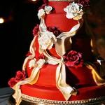 Красный свадебный торт с бежевыми лентами и розами
