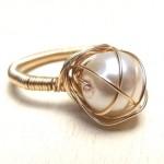 Крупная жемчужина в в золотых нитях на кольце невесты