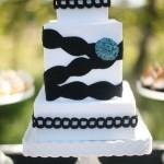 Белый свадебный торт с черной лентой и синим цветком