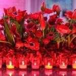 Алые цветы и свечи в композиции